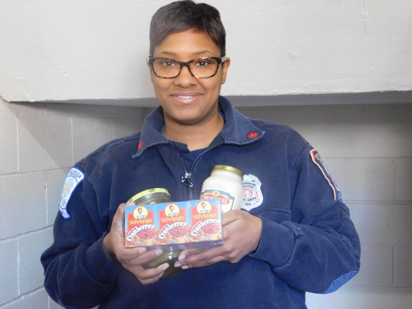 Kamisha Sims with the Decatur Fire and Rescue Department holds some of the donated items collected by the department.